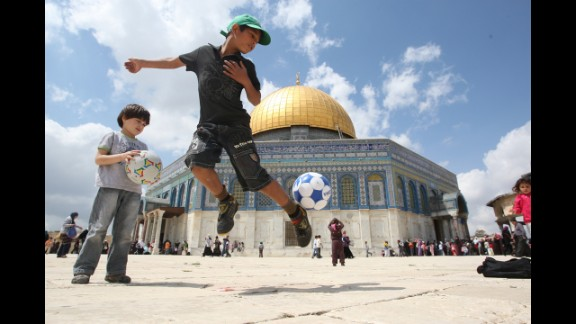 A young boy plays with a soccer ball in front of Jerusalem's Dome of the Rock mosque on April 8, 2010. AFP PHOTO/AHMAD GHARABLI (Photo credit should read AHMAD GHARABLI/AFP/Getty Images)