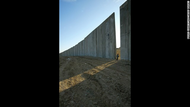 A child walks through a gap in the concrete blocks of a security wall in the West Bank village of Eizariya, east of Jerusalem, in a 2003 file photo. Take a walking tour of East Jerusalem, or a pilgrimage to the Palestinian city of Bethlehem and you'll run into Israel's infamous security barrier.