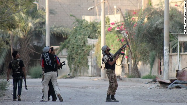 A rebel fighter points his weapon at Syrian regime forces in Deir ez-Zor on September 2.