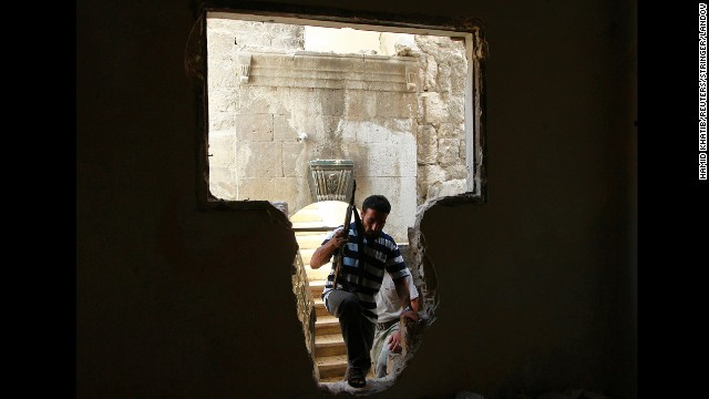 A Free Syrian Army fighter walks through a hole in a wall in Aleppo on September 3.