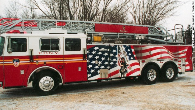 A firetruck that features a mural depicting a firefighter raising the flag is unveiled to the public in Clintonville, Wisconsin, on January 20, 2002. The truck was donated to the New York Fire Department.