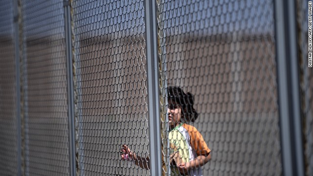 A Syrian girl stands behind a fence at Bulgaria's shelter near Lyubimets on August 28. More than 3,100 immigrants -- half of them Syrians -- have crossed into Bulgaria from neighboring Turkey this year, doubling their numbers compared with 2012 and and causing Bulgaria's few temporary accommodation facilities to overflow.