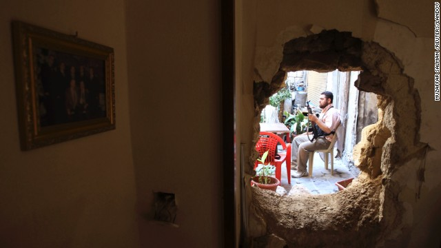 A Free Syrian Army fighter is seen through a hole in a wall of a building in Aleppo on September 3.