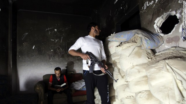 A Free Syrian Army fighter looks through a hole from behind sandbags, while a fellow fighter reads the Quran in Deir Ezzor, Syria, on Tuesday, September 3. The United States and other Western nations blame the Assad regime for a chemical weapons attack that's believed to have killed more than 1,400 people.