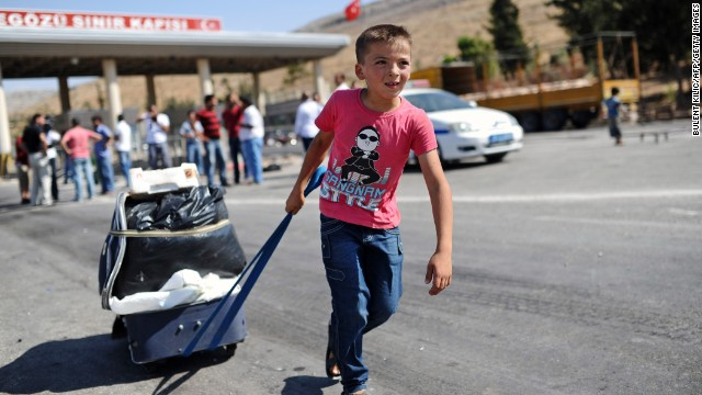 A child pulls a suitcase as Syrian refugees arrive at the Cilvegozu crossing gate of Reyhanli in Turkey's Hatay province on Saturday, August 31.