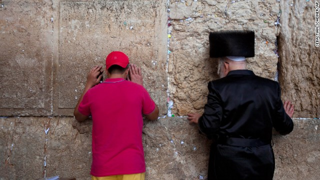 A tourist prays alongside an Orthodox Jewish man at the Western Wall on September 4.