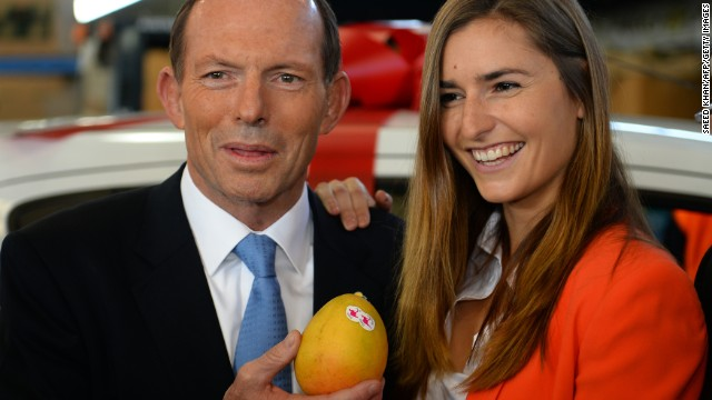 Australian opposition leader Tony Abbott poses with a mango and one of his
