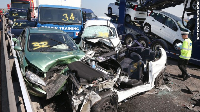 A police officer inspects the site of the major traffic accident. At least 100 vehicles smashed into each other in a massive pileup on Thursday, September 5, on a multilane bridge and highway in England's southeastern county of Kent, police said, injuring eight people seriously and leaving dozens with minor injuries.