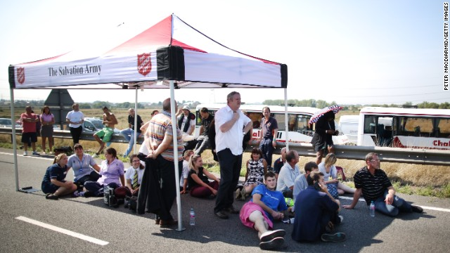 Drivers shelter from the sun under a tent provided by The Salvation Army as they wait to recover their vehicles.