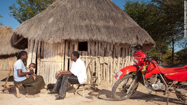 Palikobila Mwembe, an environmental health technician in the Binga district of Zimbabwe who takes part in the Riders for Health program, talks with a mother about her baby.