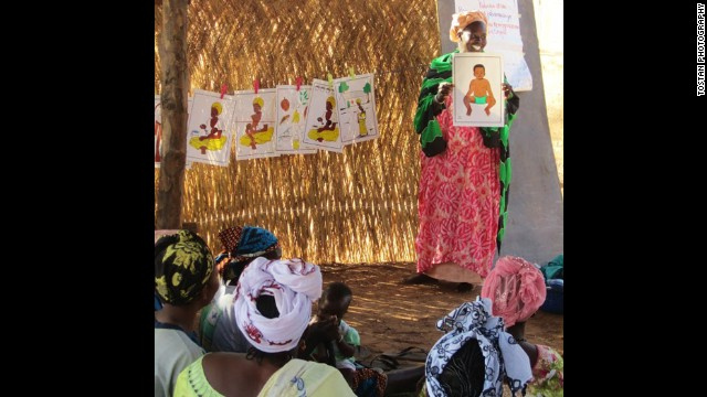 "A participant in a program sponsored by Tostan in Mali teaches infant care. Molly Melching, founder of Tostan, has lived and worked in Senegal since 1974. Her early experience working with children in Dakar and living in a rural village reinforced her belief that many development efforts did not address the true needs of African communities. She and villagers began to develop a learning program using African languages and traditional methods of learning. To date, more than 2 million people have been reached indirectly through this ""organized diffusion"" model."