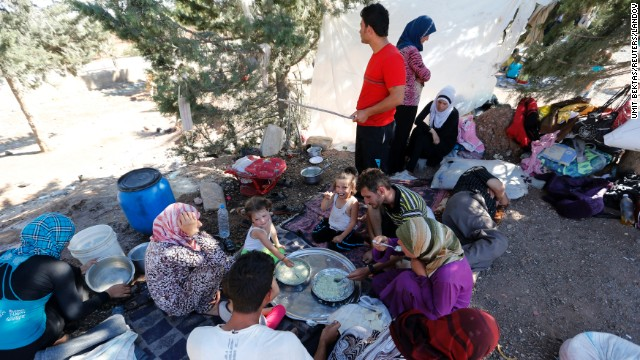 Syrian refugees who failed to find shelters in a refugee camp eat and rest by the side of a road a few meters away from the Turkish-Syrian border on Thursday, September 5.