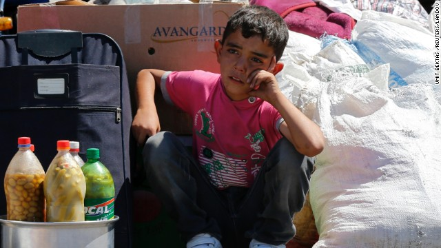 A Syrian boy sits beside his family's belongings on Friday, September 6, as they wait for a vehicle to pick them up after entering Turkey from the Turkish border gate of Cilvegozu.