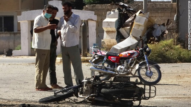 Men observe the wreckage of a motorbike in the Syrian province of Idlib on September 5. The Syrian Observatory for Human Rights watchdog said that Syrian war planes bombed rebel-held areas in Idlib, Aleppo, Hama and Lattakia.