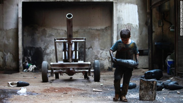 A boy named Issa, 10, carries a mortar shell in a weapons factory of the Free Syrian Army in Aleppo on Saturday, September 7. The boy works with his father in the factory.