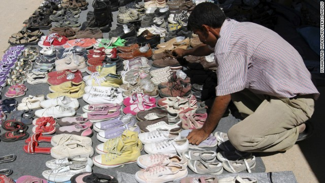 A Syrian refugee displays second-hand shoes for sale at the main market at the Zaatari refugee camp near Mafraq in September 2013.