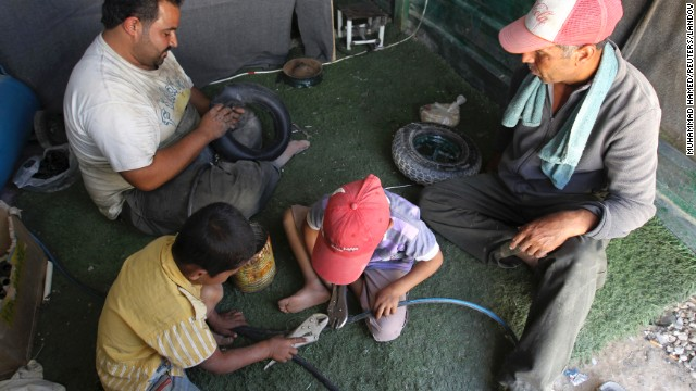 Syrian refugee workers fix cart wheels at their shop at the Zaatari Refugee Camp on September 8. Jordan has 515,000 registered Syrian refugees.