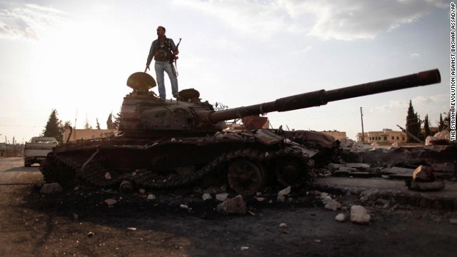 A Free Syrian Army fighter stands on a damaged military tank in Zabadani near Damascus on Sunday, September 8.