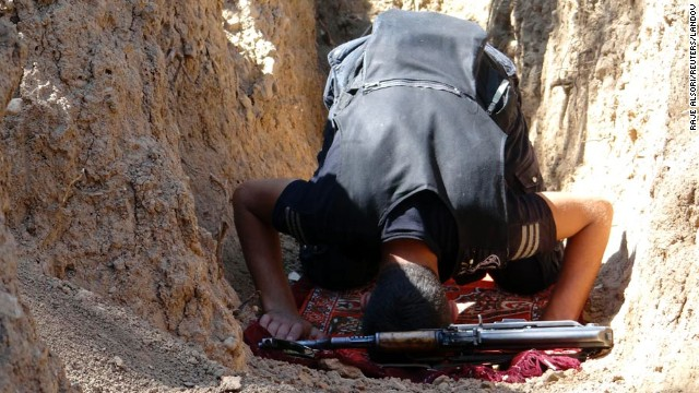 A Free Syrian Army fighter prays in a trench in the Damascus suburbs on September 8.
