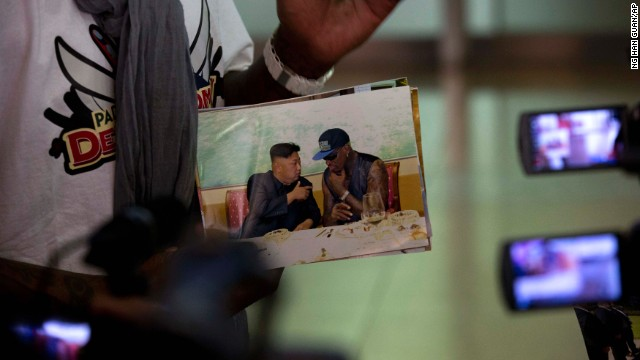 "Rodman shows a photo of himself with North Korean leader Kim Jong Un as he arrives at the Beijing airport on September 7 on his return from North Korea. At a news conference Monday, September 9, he called Kim a ""very good guy."""