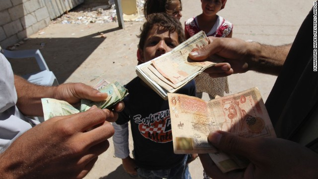 A refugee money-changer exchanges currency at the main market at the Zaatari refugee camp near the Jordanian city of Mafraq on Sunday, September 8.