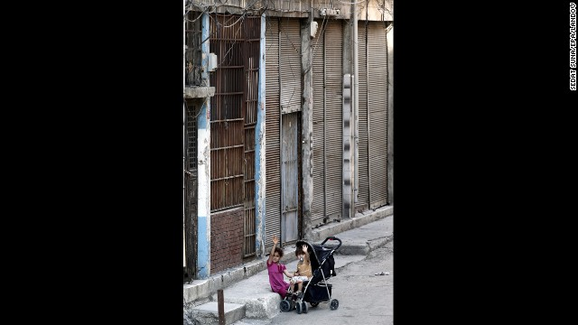Two Syrian refugee children sit outside a house where they currently live in Istanbul on September 9.