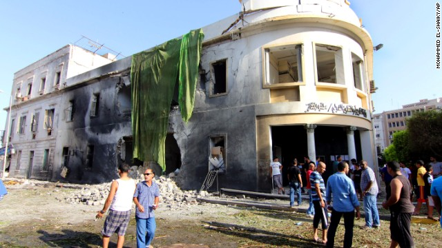 People gather to look at the site of a car bombing in Benghazi, Libya, on Wednesday, September 11. The bomb went off outside a Foreign Ministry building, state media said, one year after an assault on the U.S. Consulate there that killed four Americans, including Ambassador Christopher Stevens.