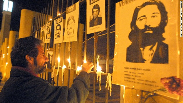 A man lights a candle at the gates of the National Stadium on September 11, 2002 in Santiago bearing pictures of those who disappeared under the 1973-1990 dictatorship of Pinochet.