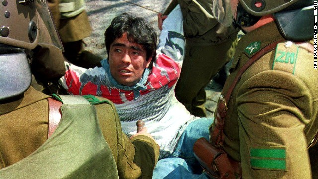 A man is arrested and carried by Chilean riot policemen as hundreds of students protest on September 11, 1993 in Santiago, Chile, during a march organized by leftists parties on the 20th anniversary of the military coup. Police stopped the marchers from reaching the La Moneda Presidential Palace.