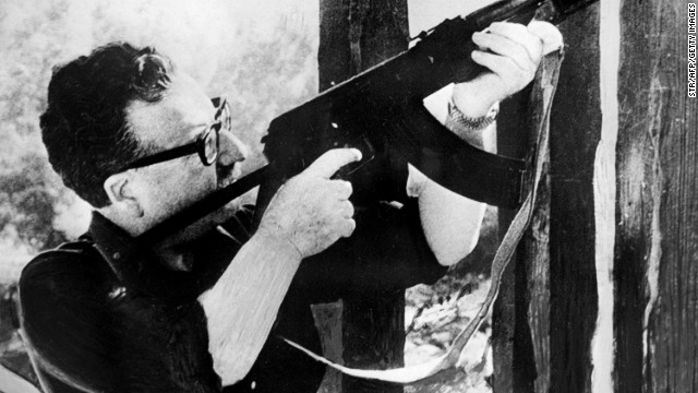 This picture taken circa 1971 in Santiago, shows Chilean President Salvador Allende testing a Kalashnikov machine gun given to him as a gift by the then-Cuban President Fidel Castro.