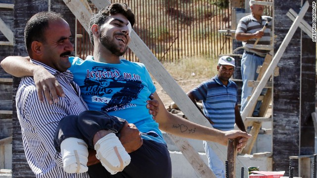 Mustafa Abu Bekir, who was wounded while fighting with the Free Syrian Army, smiles as he meets relatives after crossing the Cilvegozu gate border in Turkey's Hatay province in September 2013.