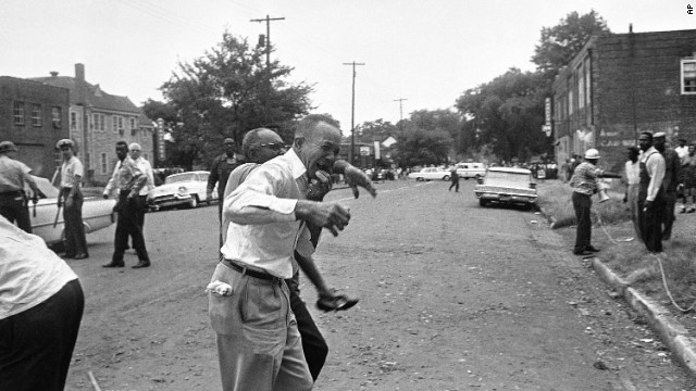 A grieving relative is led away from the site of the 16th Street Baptist Church bombing in Birmingham, Alabama, on September 15, 1963. Four black girls were killed and at least 14 others were injured, sparking riots and a national outcry.