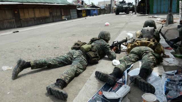 Government soldiers take cover from rebel sniper fire during heavy fighting in Zamboanga City on September 12.