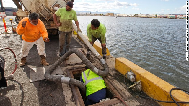 Workers from Pacific Environmental pump out the broken Matson pipeline, located under the neighboring Horizon shipyard dock in Honolulu, on September 11.