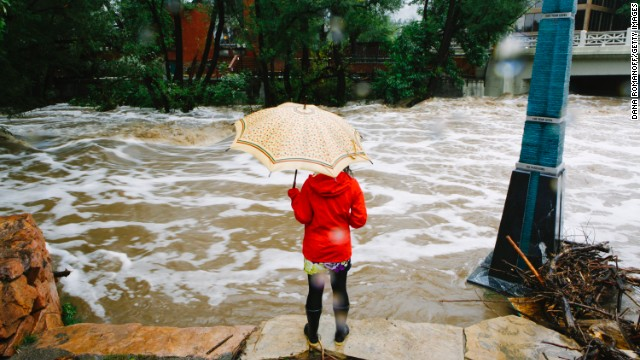 A woman looks at the flooded Boulder Creek on September 12.
