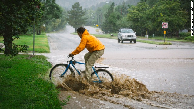 Joey Schusler rides through flooded Canyon Boulevard in Boulder, on September 12.