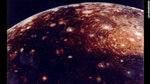"This image of Jupiter's moon ""Callisto"" was captured from a distance of 350,000 kilometers. The large ""bull's-eye"" at the top of the image is believed to be an impact basin formed early in Callisto's history. The bright center of the basin is about 600 kilometers across and the outer ring is about 2,600 kilometers across."