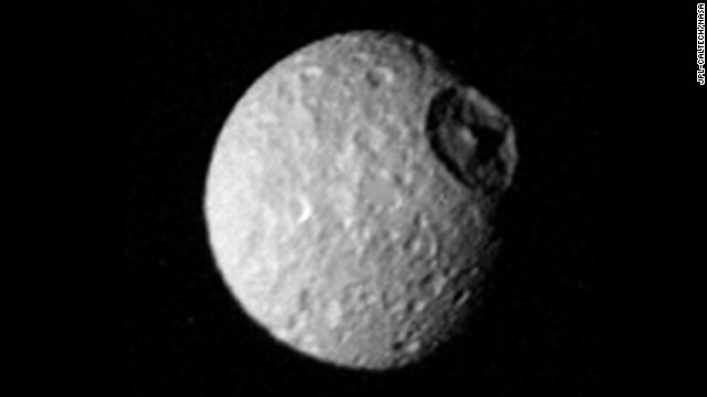 "The cratered surface of Saturn's moon ""Mimas"" is seen in this image taken by Voyager 1 on November 12, 1980. Impact craters made by the infall of cosmic debris are shown; the largest is more than 100 kilometers (62 miles) in diameter and displays a prominent central peak."
