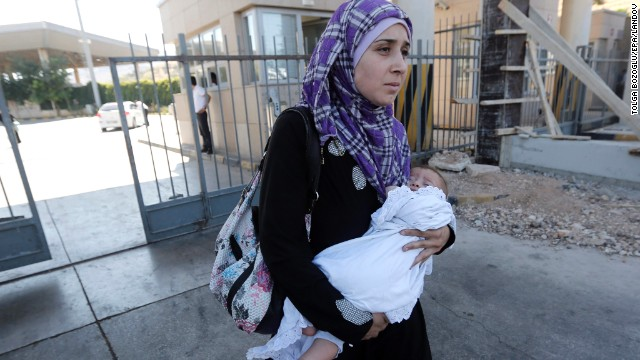 A Syrian woman carries her baby across the border into Turkey at the Cilvegozu border gate in Reyhanli, Hatay, Turkey, on Thursday, September 12.