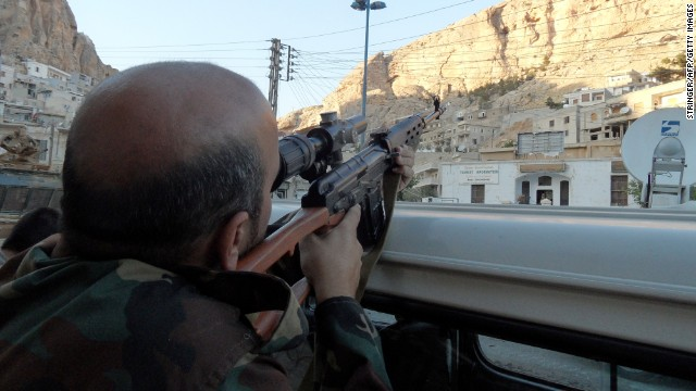 A Syrian pro-government soldier aims his rifle as he patrols the streets of the Christian town of Maalula on Wednesday, September 11.