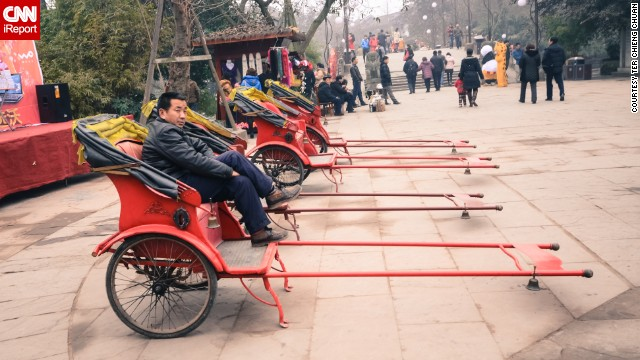 A rickshaw driver relaxes while awaiting customers in this popular tourist town near Chengdu.