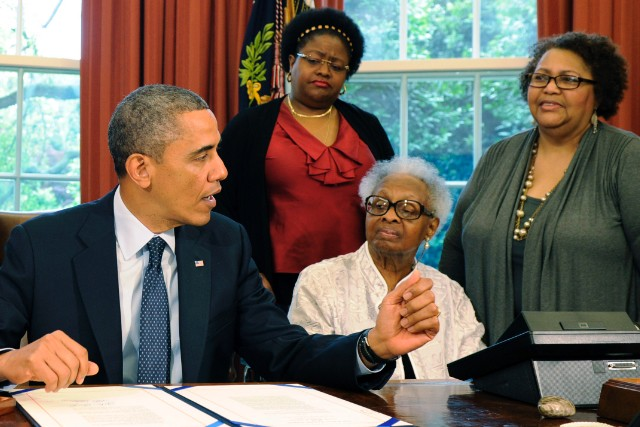 Lisa and Maxine McNair, Dianne Robertson Braddock (L-R) watch the president approve posthumous medals.