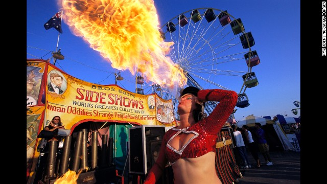 Luring in a crowd, performer Danielle De Meux blows a ball of fire outside the Bros. Grim side show tent on July 26, 2003, on the Seaside Heights boardwalk.