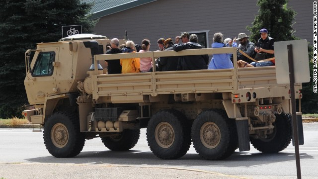 Residents ride in the back of an LMTV while being evacuated to Longmont on September 13.