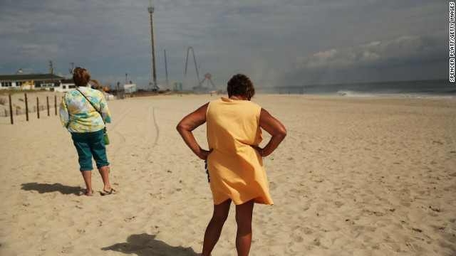 Two women take in the scene at a distance as smoke rises from the boardwalk on September 13.