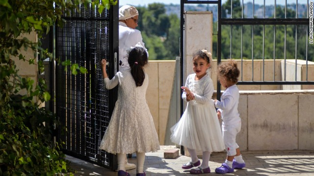 Girls open a gate for a woman in Jerusalem during Yom Kippur on Saturday, September 14. Yom Kippur is Judaism's day of atonement, when devout Jews ask God to forgive them for their transgressions and refrain from eating and drinking, attending intense prayer services in synagogues.