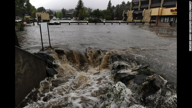 Water pours out of a parking lot, overwhelming a culvert heading under the roadway, in Estes Park, Colorado, on September 15.