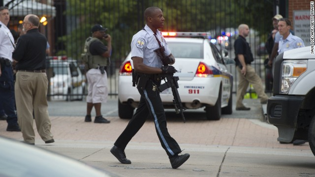 A police officer carries an automatic rifle at the Washington Navy Yard.