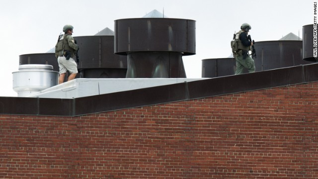 Police officers walk on a rooftop at the Washington Navy Yard on Monday, September 16, after a <a href='http://www.cnn.com/2013/09/16/us/dc-navy-yard-gunshots/index.html'>shooting rampage</a> in the nation's capital. At least 12 people and suspect Aaron Alexis were killed, according to authorities.