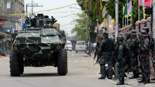 An armored personnel carrier passes by a group of soldiers. The Philippine military launched a helicopter assault on September 16 on Muslim rebels occupying parts of a major southern city.
